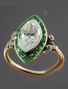 An Edwardian gold, platinum, diamond and emerald ring, French, circa 1910. Centring a 2.50ct marquise diamond framed by emeralds mounted in platinum and gold.