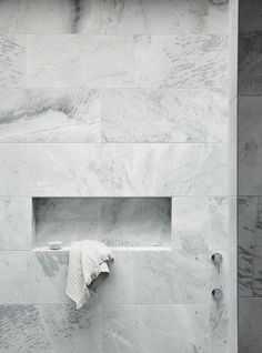 Large marble-ish tile with an inset shelf in the shower.