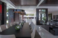 salle à manger moderne sombre aménagée avec une table rectangulaire en bois sombre, chaises blanches et suspensions rondes noires