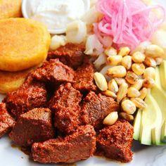 Carne colorada {Carne adobada con achiote} con llapingachos {tortillas de papa}, mote, tostado, salsa de queso, cebollas curtidas, y aguacate  Receta: http://laylita.com/recetas/2008/02/24/carne-colorada/  #CarneColorada #ComidaEcuatoriana