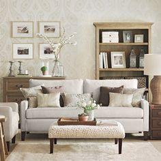 sofá no centro da sala, estante e cômoda encostada na parede, atrás do sofá