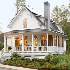 Punch Up the Porch -  Large planters filled with ferns extend a warm welcome while echoing the greens found within the landscape. Black-and-white-stripe paper lanterns bring modern appeal to this charming farmhouse.