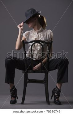 stock photo : female dancer with hat sitting on the chair over grey background