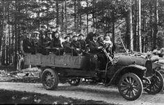 Sogn og Fjordane fylke  Dette var den første bilen A/S Fjordenes Automobilselskap kjøpte i 1913. Passasjerane er på veg til Breim, der dei skulle ta motorbåten inn til Førde. 21 personar sit på lasteplanet. Dei første bilane var små lastebilar. Når dei vart nytta til persontransport, vart det sett benkar eller stolar på lasteplanet. Olai Farsund, frå Førde, var sjåfør. Han var ein av dei dei første sjåførane i selskapet.