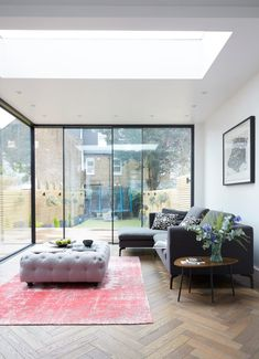 A beautiful parquet wood flooring in a light living room with plenty of glazing.