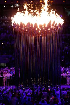 Flaming cauldron.  A series of small torches rises up to form a majestic version of the Olympic cauldron.