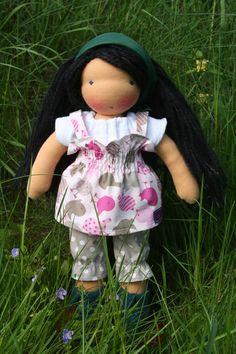 Dieses kleine Puppenmädchen nach Art der Waldorfpuppen ist 32cm groß. Sie trägt eine graue Baumwollhose mit weißen Punkten, ein weißes T-shirt aus Jer