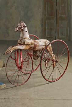 Circa 1860....Original child's tricycle with Iron frame, hand-painted rich red....Solid wood, hand-carved horse