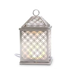 Shining openwork lantern is actually an electric warmer. The LED light glows softly through frosted glass panels while releasing the long-lasting fragrance of Scent Plus® Melts.