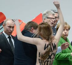 Russian President Vladimir Putin (far left) looks on Monday (8-Apr-2013) in Hanover, Germany, as one of three women who stripped off their tops protests his appearance at a trade fair. German Chancellor Angela Merkel is in the green jacket.