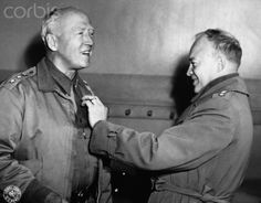 Lieutenant General George Patton receives his third star from commanding officer General Dwight Eisenhower. Ca. 1943.