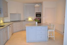 This kitchen in Woodbridge was designed for a large open plan room and is painted in subtle grey which complements the grey granite worktops beautifully.