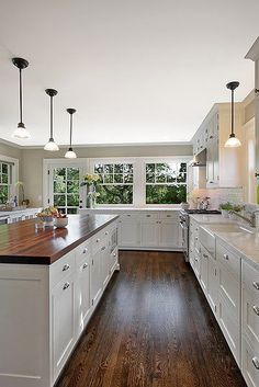 White kitchen with dark hardwood and butcher block counter tops.
