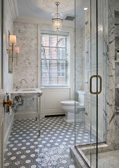 Jennifer Eisenstadt design. Stunning bathroom design with marble hex tiles on walls, white & gray hex tiles floor, marble 2 leg glass round washstand, frameless glass shower with marble slab shower surround, crown molding and pale blue painted ceiling.