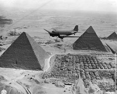 1943: A Dakota air transport plane of the US Army Air Force flies over the pyramids in Egypt, loaded with urgent war supplies