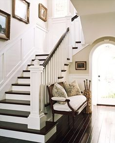 pretty foyer. dark wood, arch, stairs, bench by queen