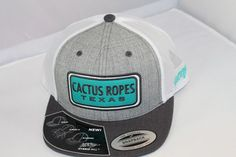 Cactus Ropes Texas Applique on Front - Heather Gray and white with greenish colors - Classic Mesh Trucker Styling - SnapBack Adjustable Sizing 63% Polyester 34% Cotton 3% PU Spandex - Hybird visor - P