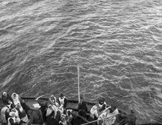 An uncrowded lifeboat of the Titanic being rowed slowly towards the RMS Carpathia immediately before the rescue of the passengers.