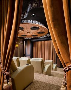 Thick, velvet curtains with tasseled tie-backs can be used to effectively close off the home theater from the rest of the basement. The most stunning feature of this room is the custom movie-reel ceiling.