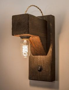"""""""The Hangman"""", was inspired by the classic word game. This rustic wall sconce includes a dimmable Edison bulb """"hung"""" below a protruding 4x4 beam. The exposed cloth covered rope wire loops over the top"""