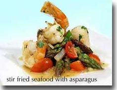 """Healthy Sautéed Seafood with Asparagus / 1 med onion 1 TBS chicken or vegetable broth 1 TBS minced fresh ginger 3 medium cloves garlic 2 cups fresh sliced shiitake mushrooms 1 bunch thin asparagus, cut in 2"""" lengths  1/4 cup fresh lemon juice 2 TBS soy sauce) 2 TBS mirin wine pinch red pepper flakes 3/4 lb cod fillet cut into 1 inch pieces 8 large scallops 8 large shrimp, peeled and deveined 1 cup cherry tomatoes cut in quarters 1/4 cup chopped fresh cilantro salt and white pepper to taste"""