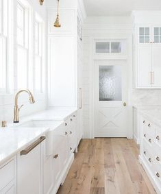 Heres a white kitchen with a lighter floor but wide planks