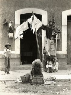 Tina Modotti - Untitled [Woman Doing Laundry in Front of Doorway with Four Children], ca. 1926-1929 - Gelatin silver print
