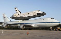 Retired Discovery Space Shuttle is conected to a Boeing 747 to fly from Florida to Washington DC.