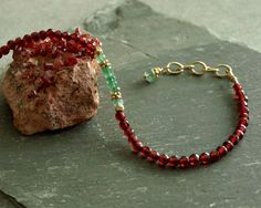 This garnet emerald bracelet has natural Zambian emeralds at its center, surrounded by small 14K gold vermeil beads and genuine faceted small deep red garnets. This Christmas colored red and green bracelet closes with a 14K goldfilled lobster clasp, with an additional larger green emerald hanging from the closure chain.  The combination of the small beautiful translucent green emeralds with the rich red garnets is gorgeous, and evokes elegant Christmas colors. The center green emeralds are…