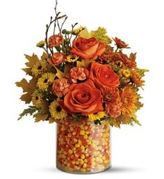 Candy Corn vase~ this is done with the candy corn in the big vase and a smaller vase with water set on top for the fresh flowers.