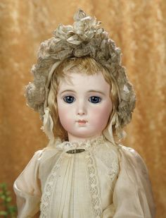 "24""-Beautiful French Bisque Bebe Triste by Emile Jumeau, Size 11~~~ Marks: 11 (head) Jumeau Medaille d'Or Paris (body). Comments: Emile Jumeau, circa 1885. Value Points: especially fine presentation of the wistful Bebe Triste look with large luminous eyes complemented by full cheeks, very plump early original body, choice bisque, lovely antique costume including leather shoes signed Bebe Jumeau 11."