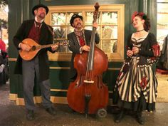 Among more than 800 costumed characters, a trio of Victorian-attired musicians entertains passersby at the Great Dickens Christmas Fair.