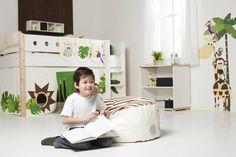 Przestrzeń pod antresolą z łóżkiem stanowi miejsce kreatywnej zabawy. Osłonięte dodatkowo ozdobnymi zasłonkami, może być dyskretnym składzikiem na zabawki. Pas imitującej drewno tapety na ścianie harmonizuje z motywami dżungli na tkaninie i naklejce.