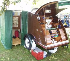 Teardrop trailer with a kitchen in the back and a changing room off to the side.