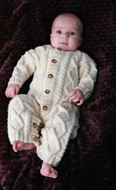 This Baby Aran Body Suit free knitting pattern is available in sizes 0-3 months, 3-6 months and 6-12 months. It features allover cable patterning and button closures.