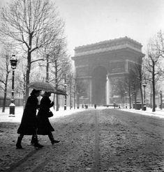 Paris sous la neige Paris en 1940 –  Des parisiennes marchent sur la neige grise, près de l'Arc de Triomphe. Déjà en 1940, la neige avait du mal à tenir au sol.
