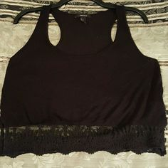 Forever 21 Racerback Crop Top Used Forever 21 black racerback crop top with floral lace trim. (Thin see through material) Size Small, but fits like a Large. (Small hole above lace trim on front & small hole in the center of the back) Forever 21 Tops Crop Tops