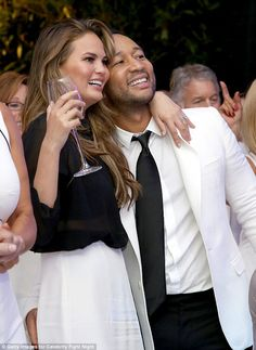 Still newlyweds! John Legend placed his hand on his wife Chrissy Teigen's bum as they atte...
