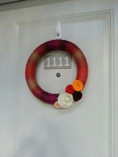 Yarn wrapped styrofoam wreath with felt flowers.