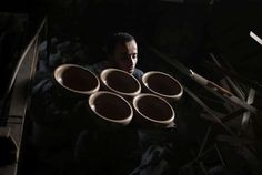 A Palestinian worker carries newly made pottery to be dried at a pottery workshop in Gaza City