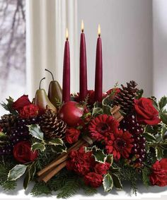 Adorn your table with this beautiful centerpiece arranged with fresh flowers, fruit and evergreens with three tall red tapers. Perfect for your holiday table.