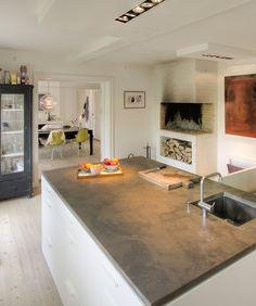 Un grand ilôt central recouvert d'un plan de travail en béton occupe la partie centrale de cette grande cuisine. Dans le coin, la cheminée permet des modes de cuisson alternatifs.