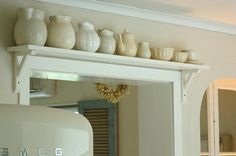 Shelving above doors gives a custom look, extra storage, and a beautiful and unique place to show your beautiful pieces, especially in the lurched.