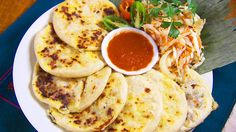 Pupusas (corn cakes stuffed with cheese) with pork, beans and a side of shredded cabbage and carrot.