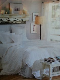 Distressed mantle above bed, creamy pillar candles, all white bedding