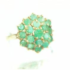 An original ring which is fully hallmarked for 1976. This genuine piece of vintage jewellery is studded with a cluster of 19 beautiful green emeralds. The cluster measures about 1.6 cms diameter. The shank is made of nine carat yellow gold, UK finger size O.5 or just over USA size 7.5. A really lovely piece of vintage jewellery