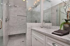 Light gray stone cover this contemporary bathroom for a stunning effect. A glass shower adds a sleek modern touch.