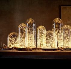 One or two similar cloches on the sofa table. These lights are the same as the ones around the mirror. They have battery packs for the 5 and 10 foot ones so no cords to deal with.
