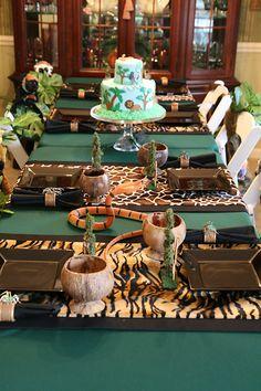 Decoración de mesa de fiesta en la selva con serpientes plásticas y enredaderas. #FiestaInfantil