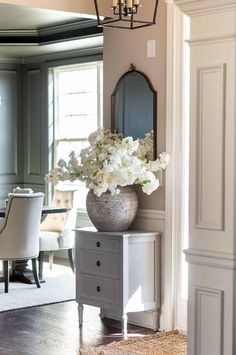 Entryway in Sherwin Williams Versatile Gray Paint -- a Warm Greige Interior Paint Color with Sherwin Williams Iron Ore Charcoal Paint in the Dining Room Background